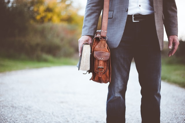 Gentleman with dark jeans and a grey blazer clutches a worn hardcover novel beside his leather satchel, as he walks along a country road.