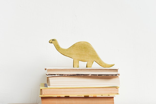 A toy dinosaur sits atop a stack of books