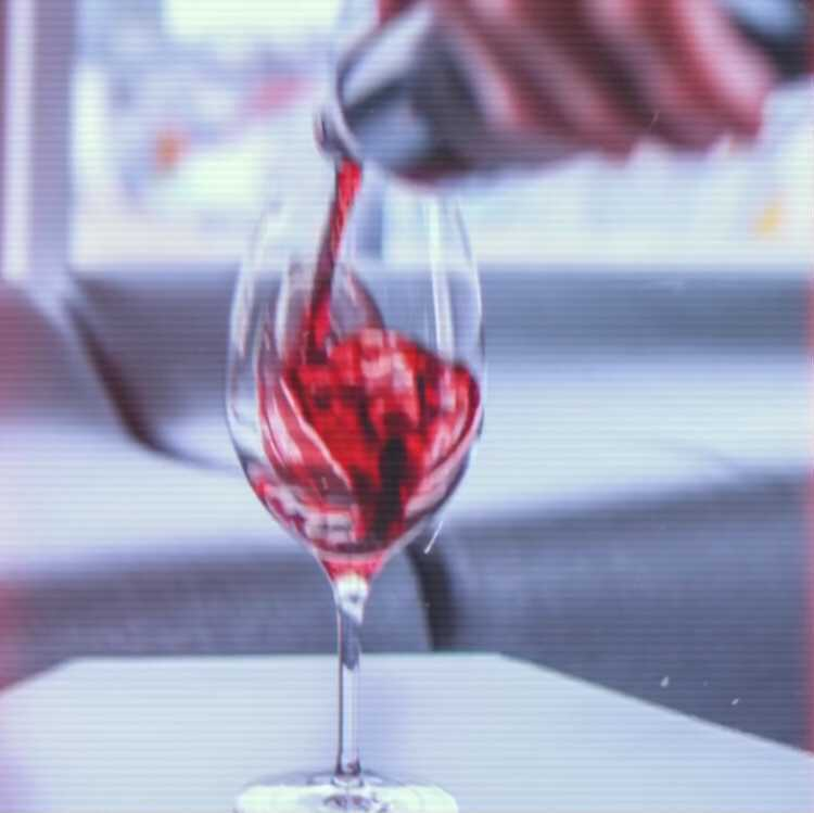 Red wine spills into a glass
