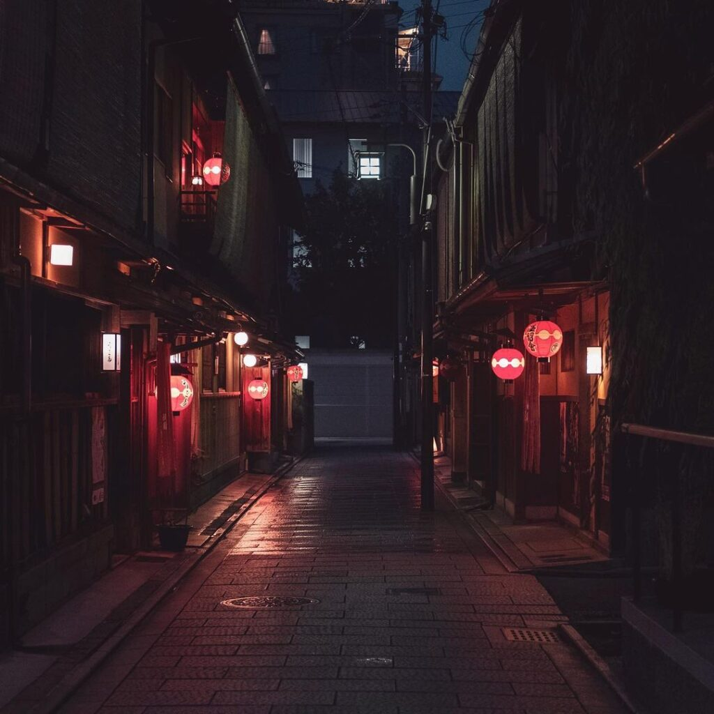 Night time in a quiet part of the city. An alley between two buildings, lined with red lanterns.