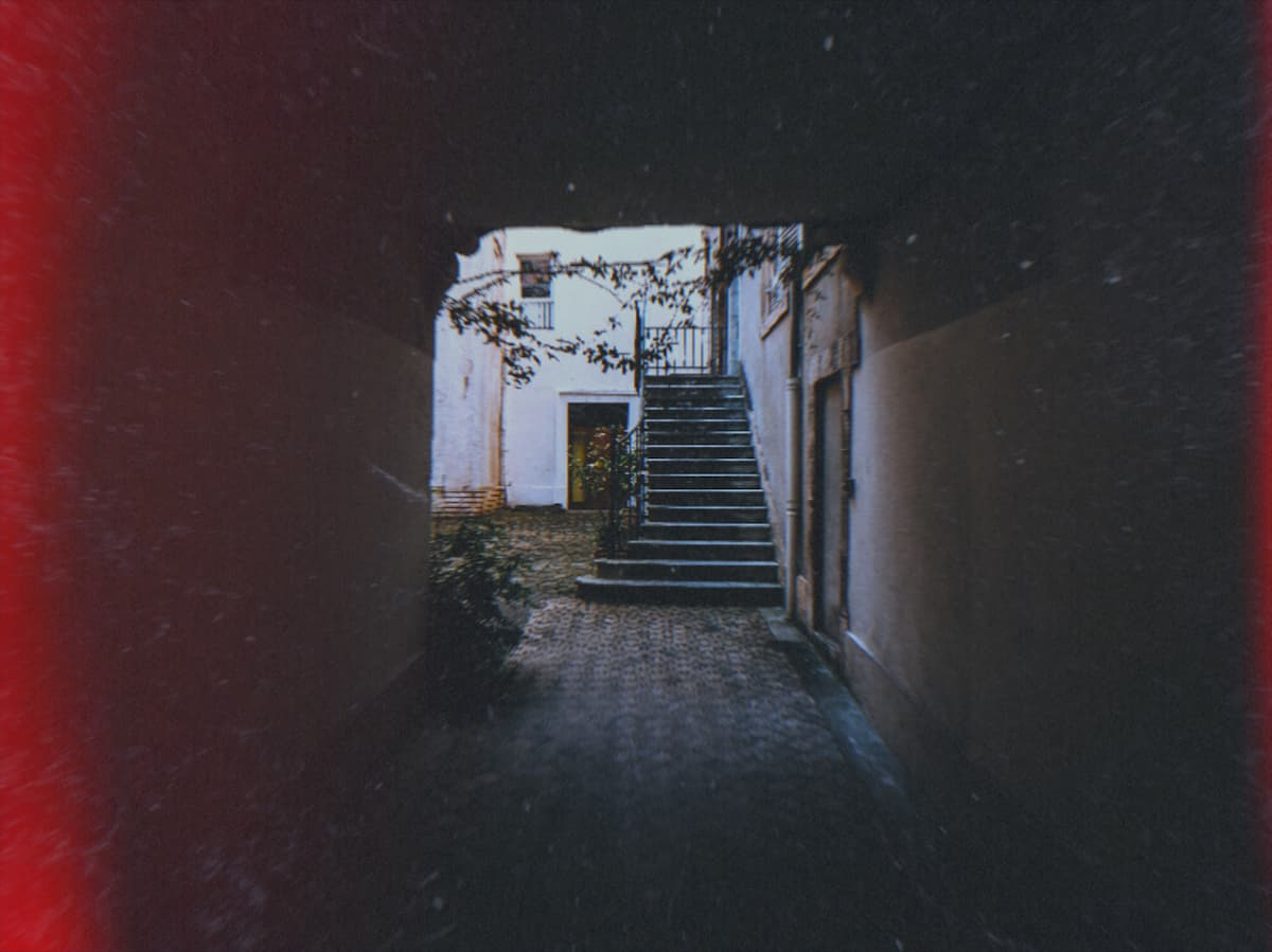A shadowy walkway leading to a courtyard with steps leading to the first floor