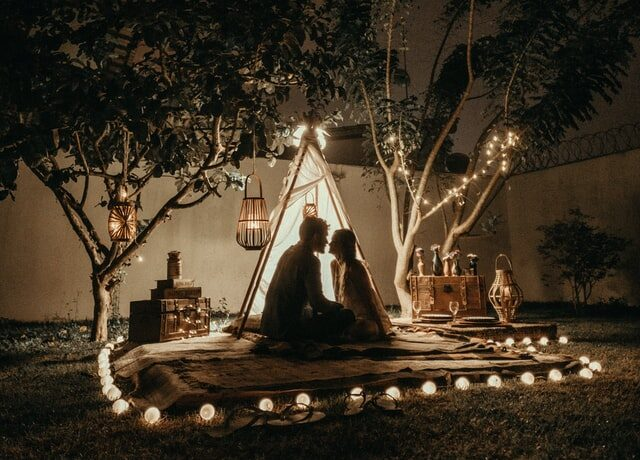 A couple sit outside a tent lit by fairy lights